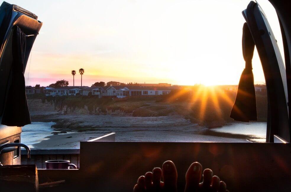 Sunrise in Santa Cruz, California, from the back of a campervan on the beach