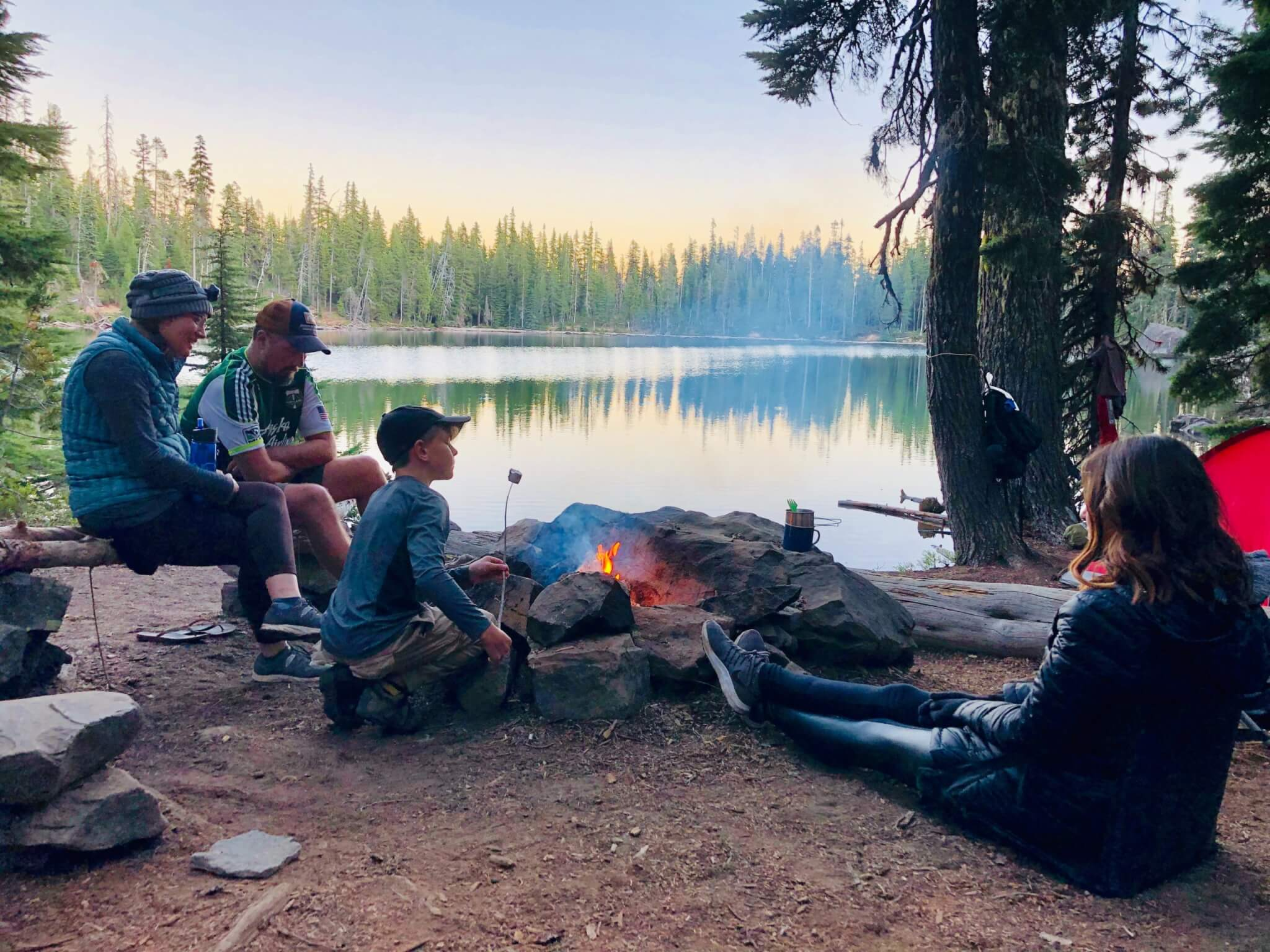 Family sitting around a campfire.