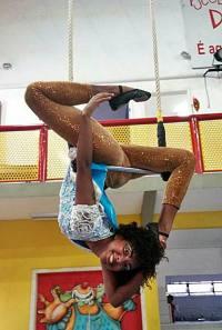 Artista da Trupe Circus no trapézio simples.