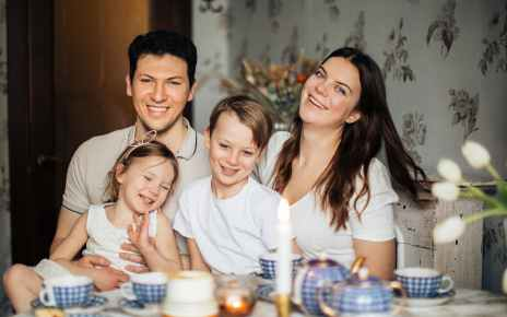 loving family laughing at table having cozy meal