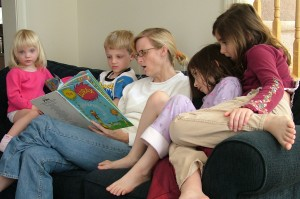 Stock photo: Mother reading a book to kids