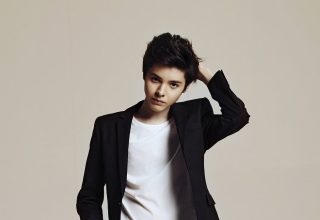 Kristian Kostov stands in front of a grey wall, posed with his left hand on his head.