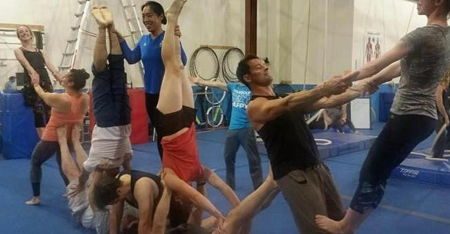group of people training partner acrobatics