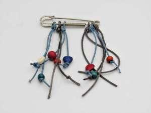 Χειροποίητη Καρφίτσα κρεμαστή με κορδόνια και χάντρες. Περίπου 7-8εκ.Χειροποίητη Καρφίτσα κρεμαστή με κορδόνια και χάντρες. Περίπου 7-8εκ.