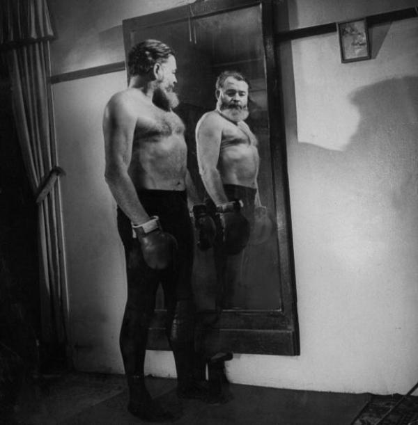 Author Ernest Hemingway admiring his mirror image, bare-chested & sporting boxing gloves. (Photo by George Karger/Pix Inc./Time Life Pictures/Getty Images)