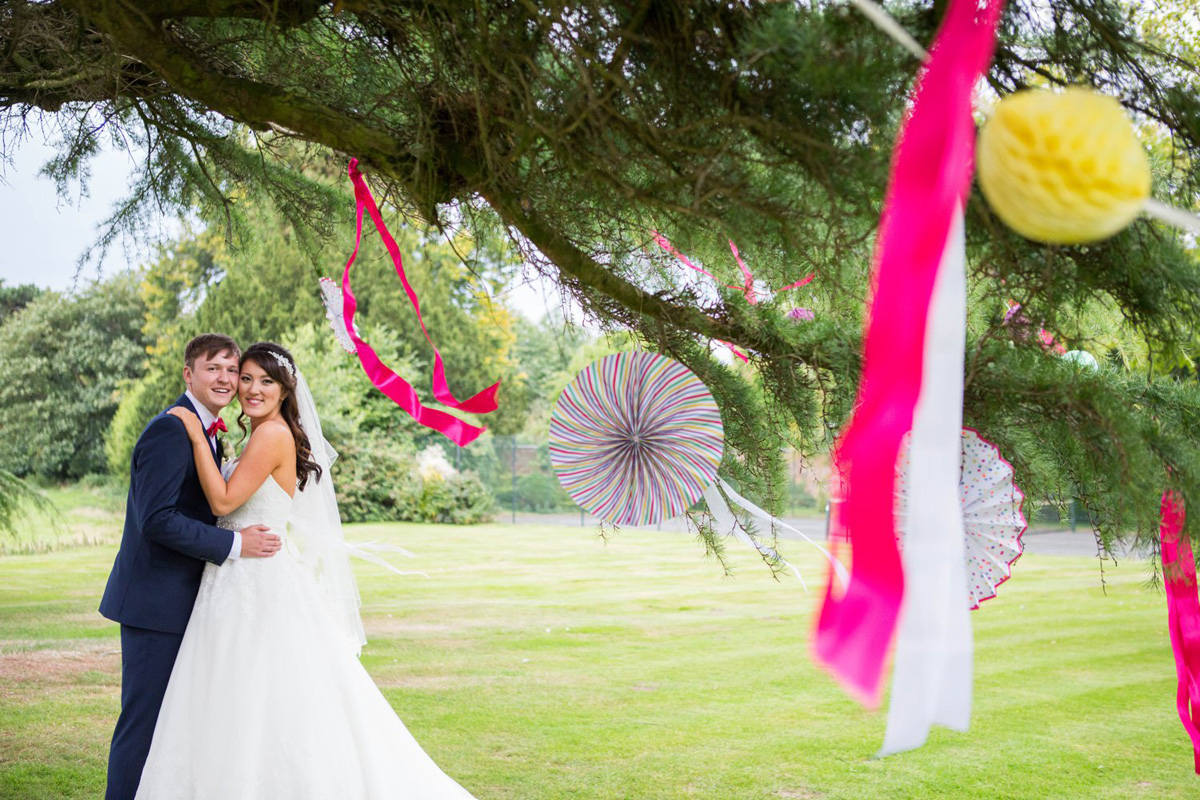 bride and groom under tree decorated with ribbons and pinwheels