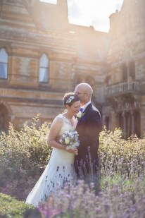 bride and groom snuggle in the gardens surrounded by lavender