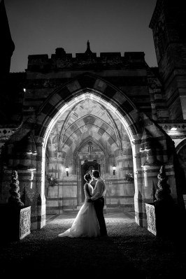 bride and groom under archway black and white night time