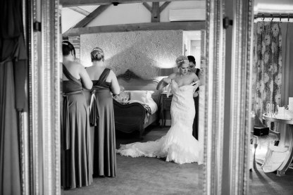 bride being helped into dress by bridesmaid at mythe barn