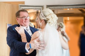 father of the bride comforts daughter on wedding morning