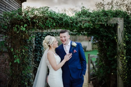 bride and groom laughing together documentary under trellis Winter Wedding Mythe Barn Warwickshire