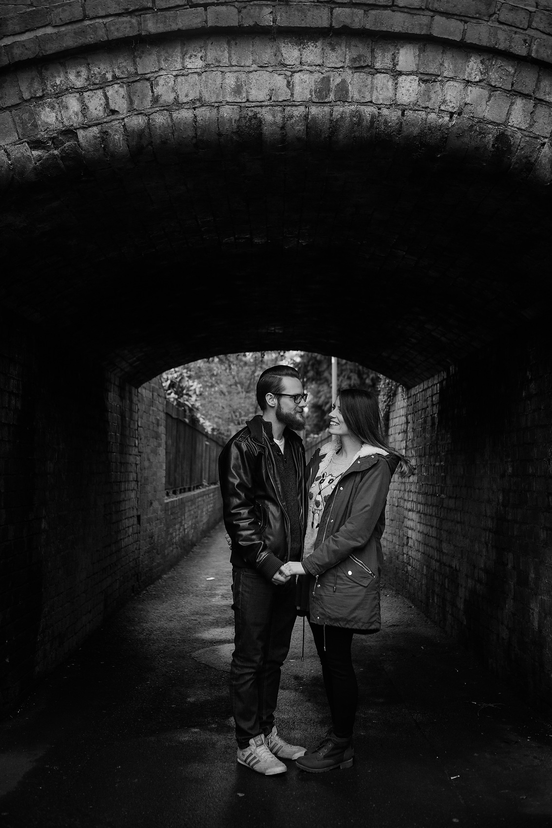 couple laugh together relaxed portraiture quirky underpass pre wedding shoot