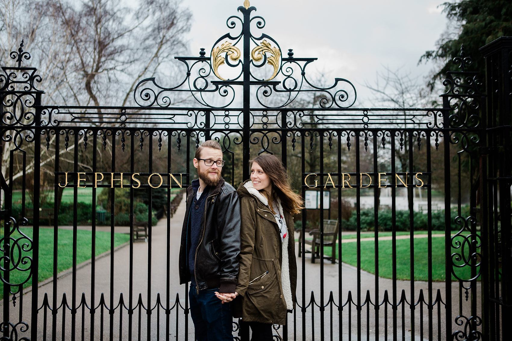 cool couple pose in front of park gates leamington spa rainy day