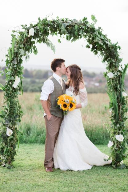 groom kisses brides forehead under flower arch