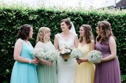bride with pastel bridesmaids laugh in garden in staffordshire
