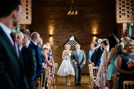 bride walks down the ailse swallows nest barn warwickshire