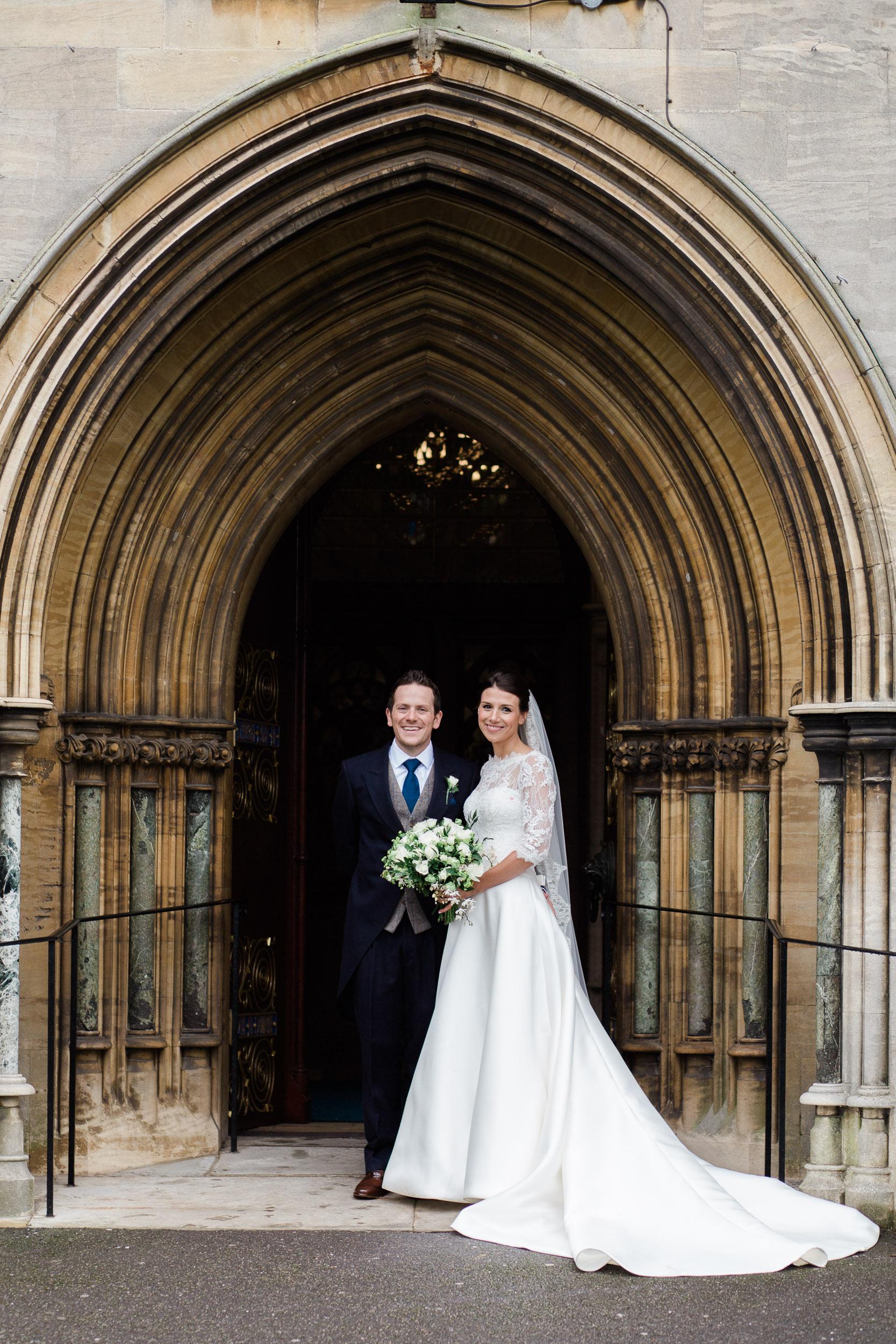 Bride and Groom pose in doorway of church