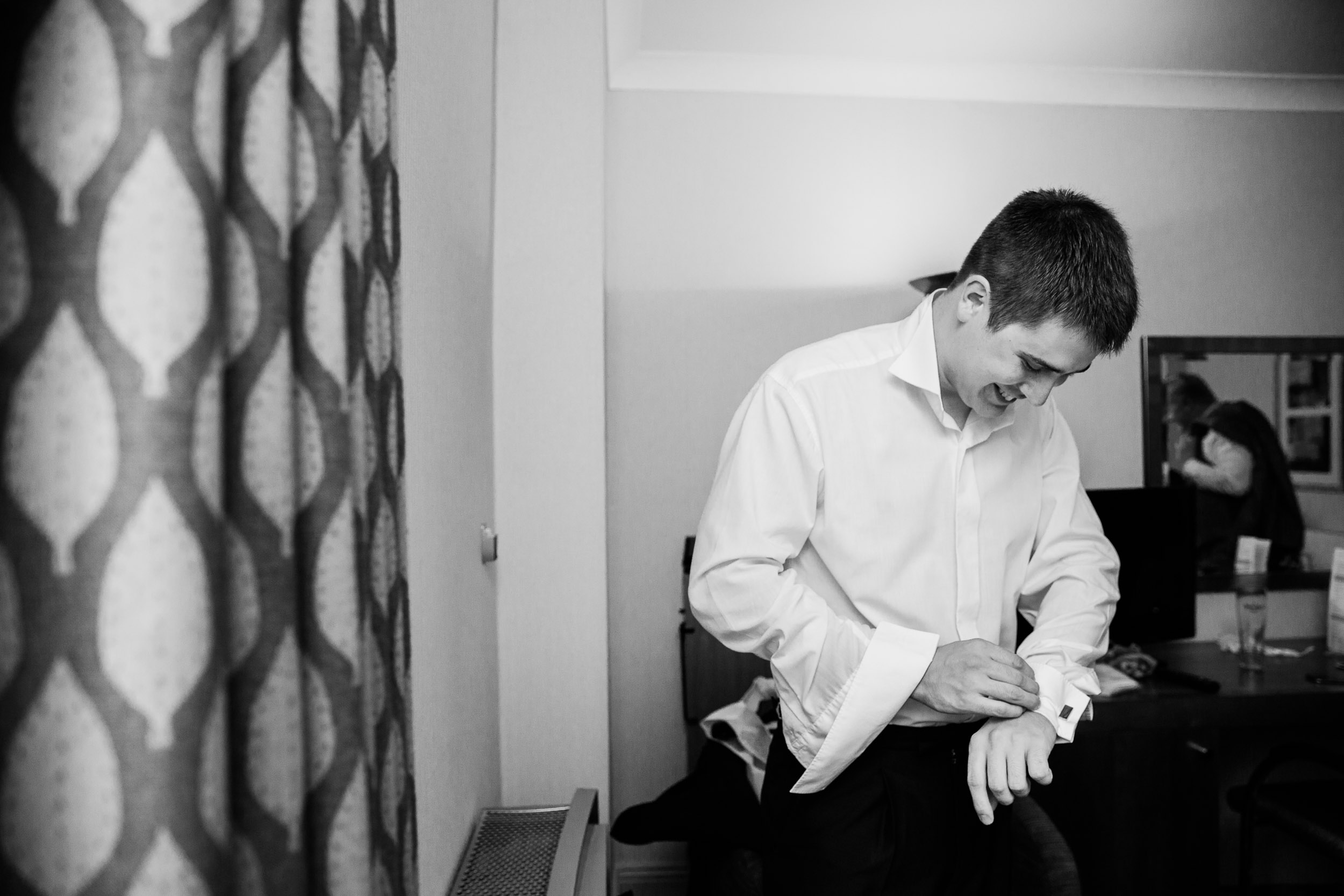 groom buttoning his shirt chesford grange hotel