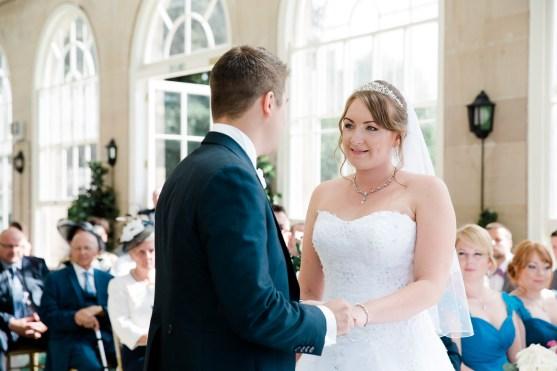 bride and groom exchange rings in the orangery