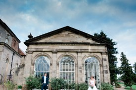 bride and groom quirky pose outside orangery