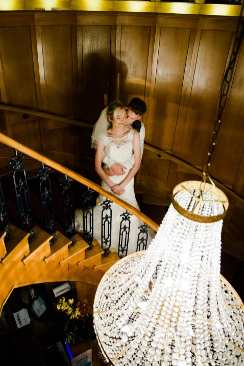 Bride and Groom on stairs with beautiful chandalier