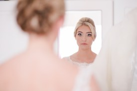 bride looking in the mirror before she leaves her house
