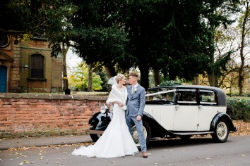 bride and groom stand with wedding car