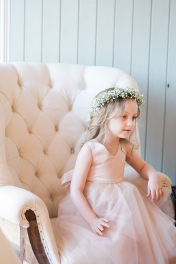 flower girl sits on seat in dressing room west mill