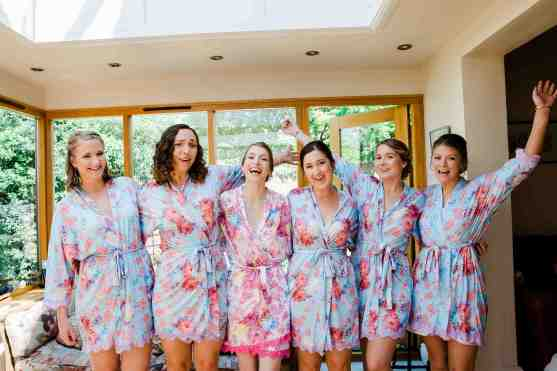 bride and bridesmaids laugh in matching dressing gowns in family home wedding morning