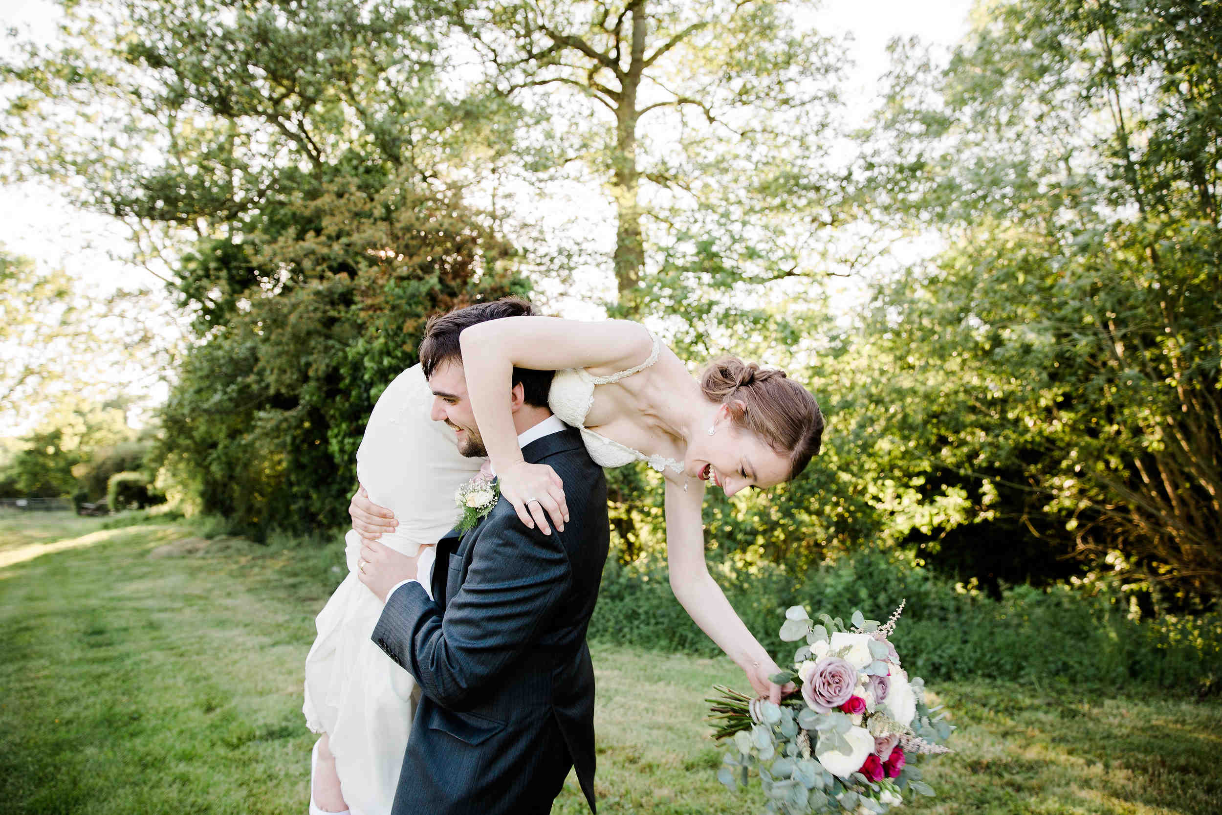 groom picks up bride and carries her away