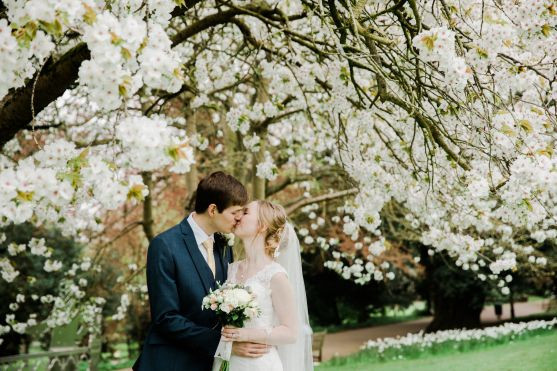 bride and groom kiss under blossom tree jephson gardens leamington spa natural relaxed wedding Leamington Spa Relaxed Church reportage photography