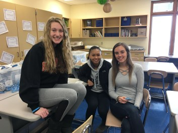 Three students sitting on a desk