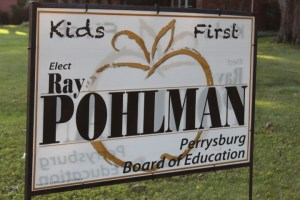 Yard sign reads Kids First. Elect Ray Pohlman Perrysburg Board of Education. Paid for by Friends of Pohlman