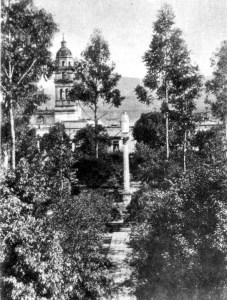 Plaza de los Mártires, columna con el monumento de Morelos en cantera, al fondo el templo de San Agustín.