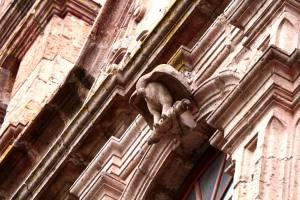Detalle de la ventana en la fachada. Es un ave (al parecer un buitre) que se devora las entrañas, señal de retroalimentación.