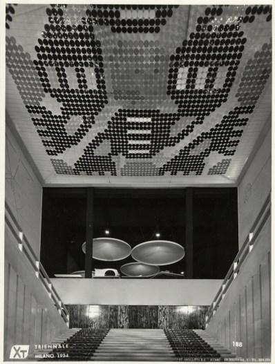 X Triennale 1954, scalone d'onore, stuoia su disegno di Giuseppe Aymone, sulla parete in fondo ante di porta su disegno di Mirko Basaldella, soffitto realizzato con dischi colorati di vetro soffiato su disegno di Giuseppe Capogrossi Foto Ancillotti