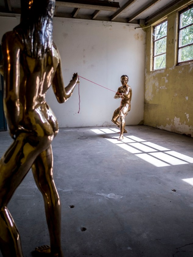 Pascale Marthine Tayou, Tug of war, 2007,Couple of bronze statues, red wool thread, Woman 160 cm, Man 155 cm © Sebastiano Pellion