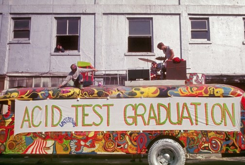 Anthony Dean Wells, known as the Hermit, paints the top of The Bus in preparation for the Acid Test Graduation celebration, while another Merry Prankster checks the musical equipment on top of The Bus. San Francisco, October 1966. | Location: outside the Warehouse, Harriet Street, South of Market, San Francisco, California, USA. (Photo by © Ted Streshinsky/CORBIS/Corbis via Getty Images)
