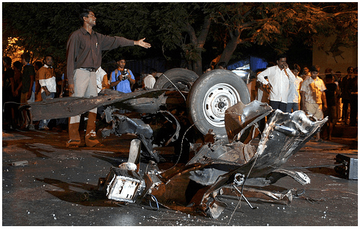 Onlookers stand at the site of a bomb blast in Mumbai November 26, 2008