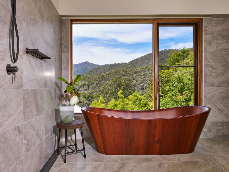 A beautifully polished red gum soaker bath faces a large glass-panelled window