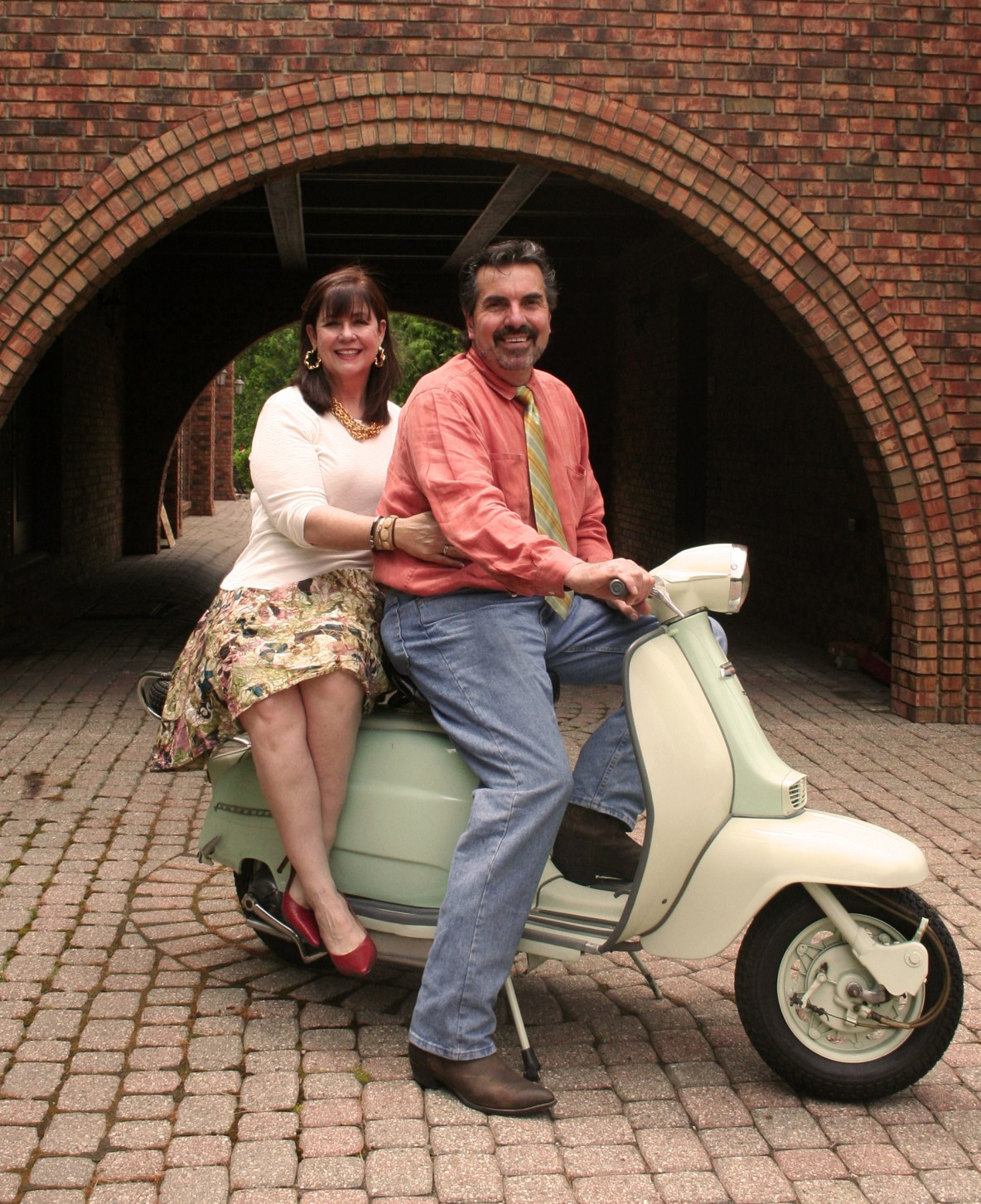 Two people sitting on moped