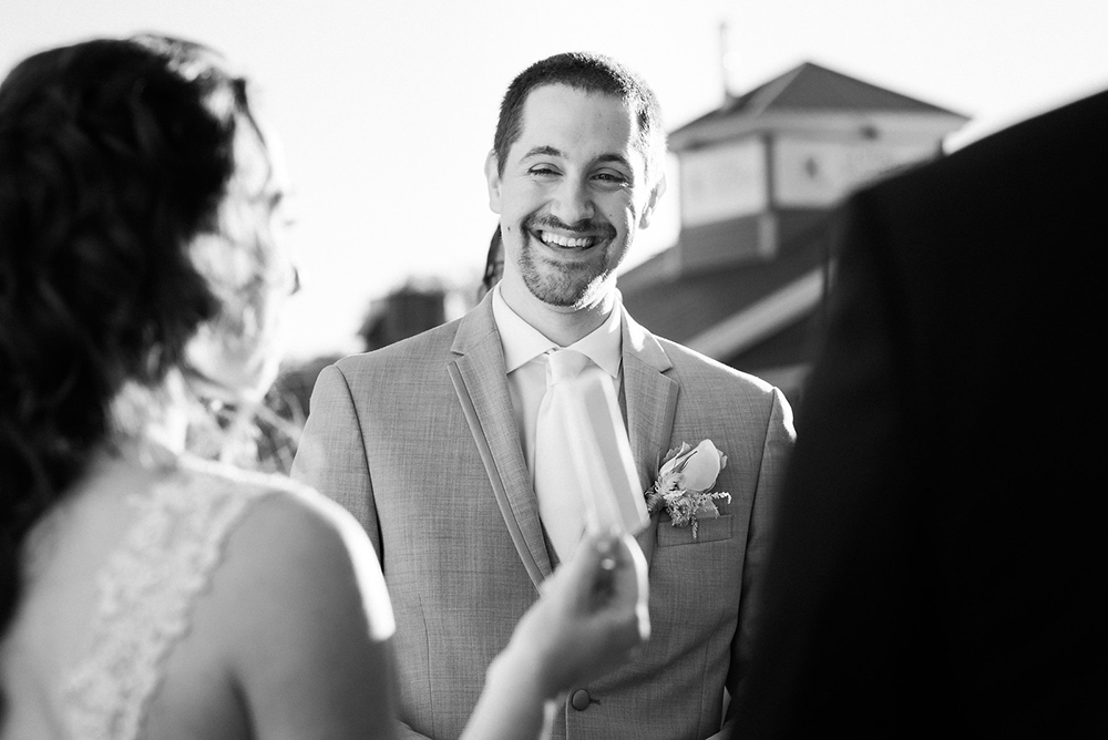 Candid photo of groom smiling during bride's vows