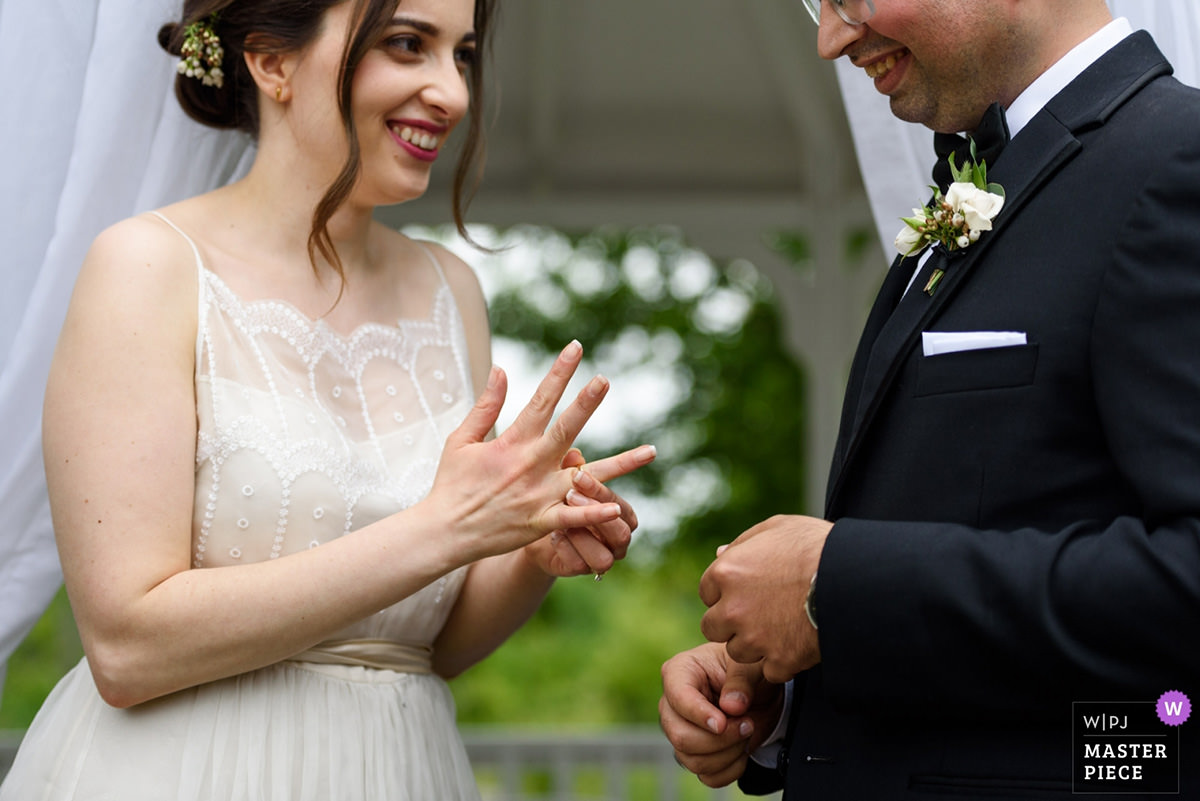 Award-winning wedding photo of bride adjusting the ring