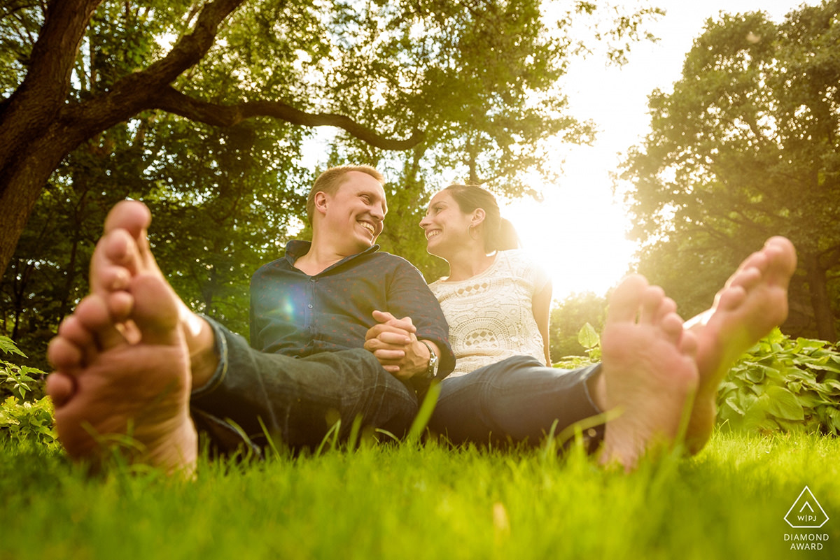 Award-winning engagement photo of couple lounging in the grass at Parc Jean-Drapeau