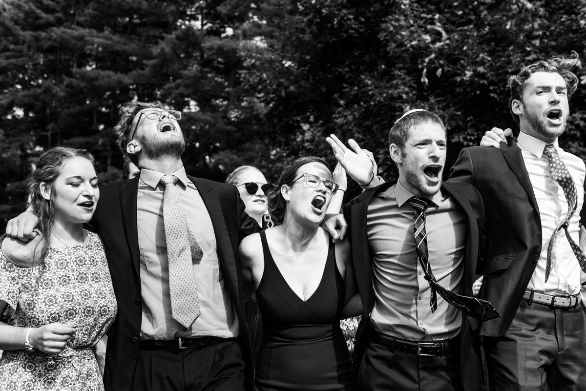 Wedding guests jumping and singing at jewish wedding