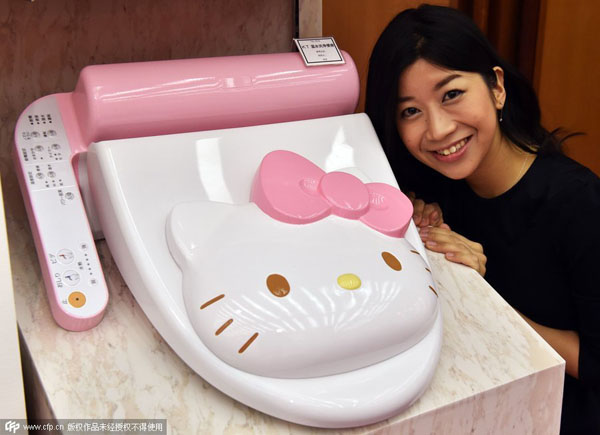 An employee for Japanese character goods maker Sanrio displays a prototype model of a Hello Kitty branded toilet seat at Sanrio's headquarters in Tokyo on February 2, 2015. The toilet seat has seat heating and warm water shower functions. AFP PHOTO / Yoshikazu TSUNO