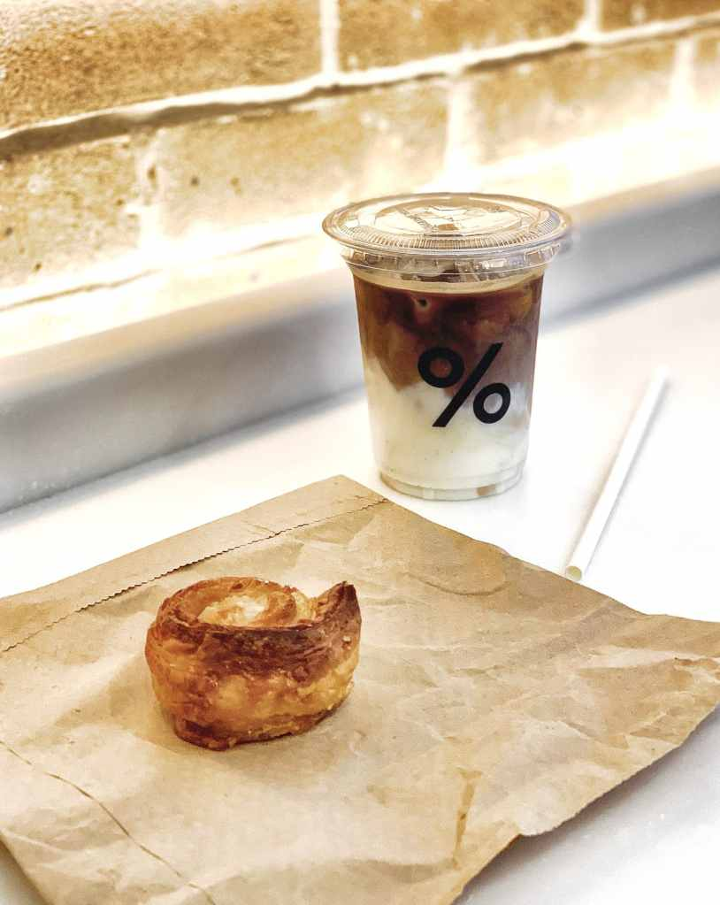 Image of a piece of % Arabica's Kouign Amman pastry and a cup of Iced Latte