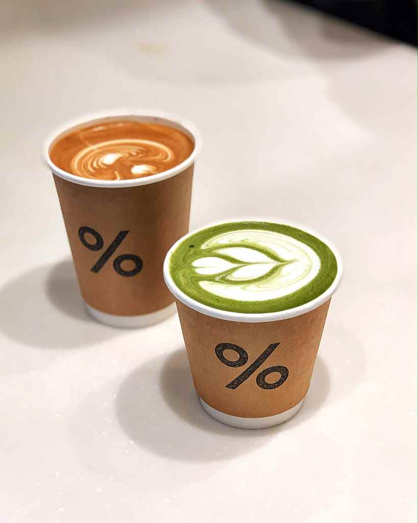 Image of a cup of % Arabica Matcha Latte and a cup of Latte