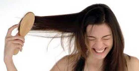 ragazza con nodi nei capelli che si pettina