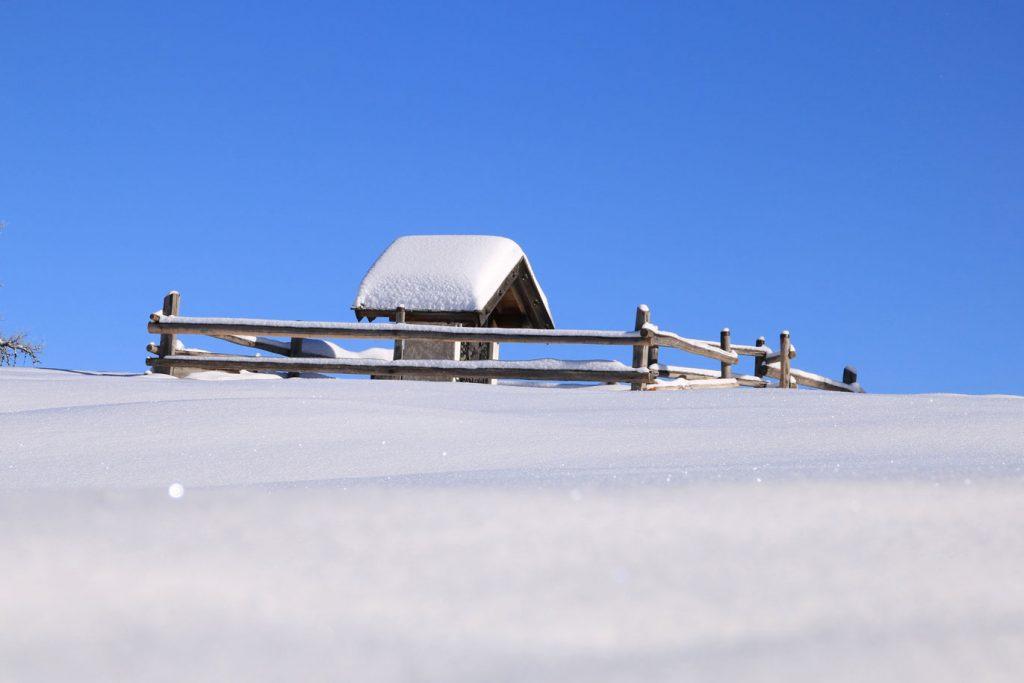 paesaggio invernale croce innevata sulla malga a meltina